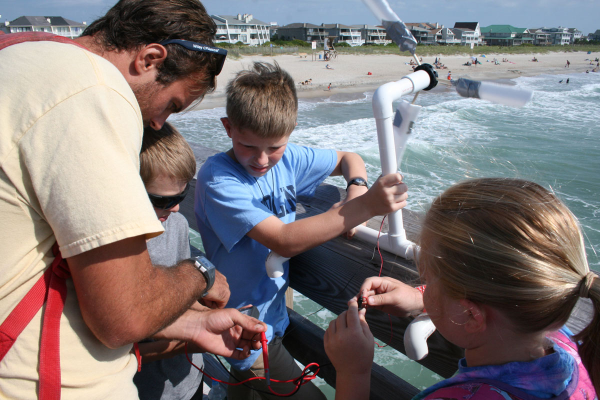 Kids and adult with hand-held wind turbine on pier above beach