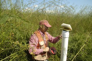 Mike Burchell checks the depth of the groundwater near the proposed restoration site. Photo Courtesy Rhett Register.