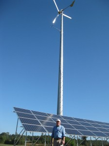 Wes Carter in front of a wind tower and solar array.