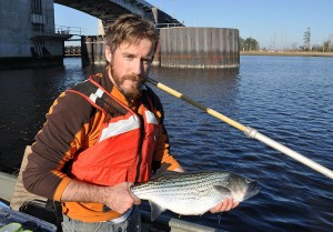 Joshua Raabe holds a tagged striped bass to release in the Cape Fear River.