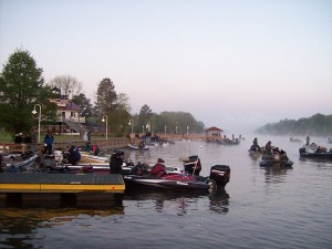 Visitors sit on boats near a dock.