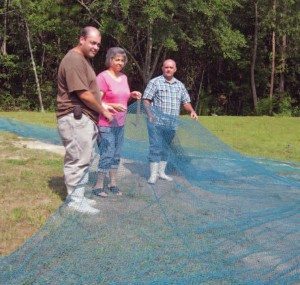 From left, Eric, Devonda and Dolphus Thompson of Sneads Ferry check nets for the family business.