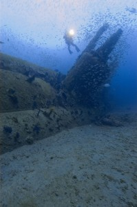 A diver hovers above the wreck of the U-352 submarine.