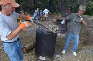 Agusta Varnam and Terrence Galloway lift grill of oysters during roast.