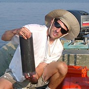 Man on boat holding up core sample.