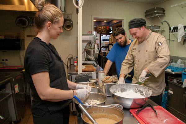 From left to right, Johanna Lachine, Justin Lachine and Eric Whidbee prepare cape shark at Café Lachine. Photo by Jim Trotman