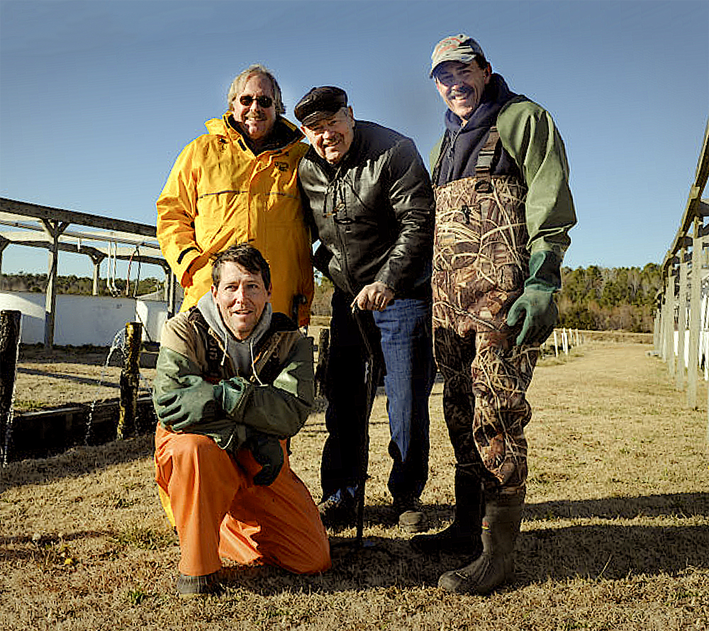 Reading and his team are the latest in a long line of pioneers at the Pamlico Aquaculture Field Laboratory. Earlier groundbreakers (right) included Craig Sullivan (back row, left), former North Carolina Sea Grant director Ron Hodson (back row, middle), Andy McGinty (back row, right), and Mike Hopper (kneeling).