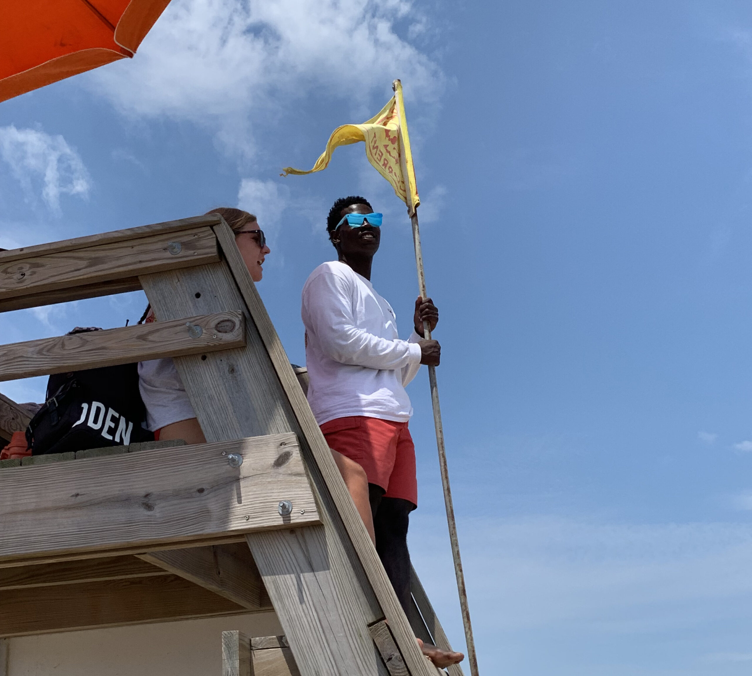 Kill Devil Hills Ocean Rescue lifeguard Reggie Kelly holds a yellow flag, warning swimmers to be cautious of strong currents.