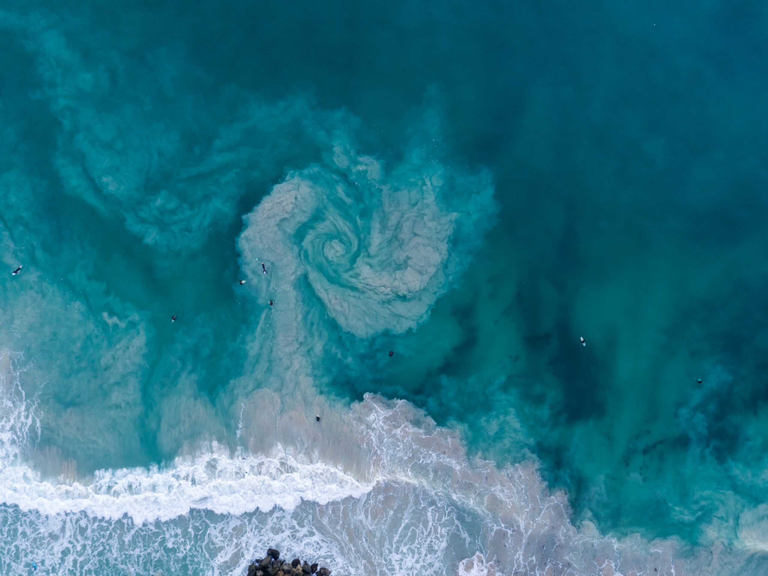 Rip currents occur on surf beaches around the globe. The rocky structure at the bottom of the frame likely contributed to this rip, photographed in Australia and distinguishable by a swirling sediment plume.