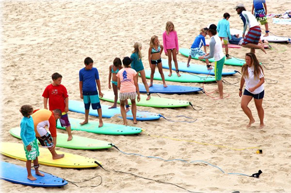 A row of students standing on surfboards on the beach