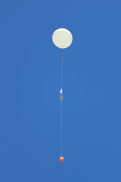 A white balloon with a red payload flying in a blue sky