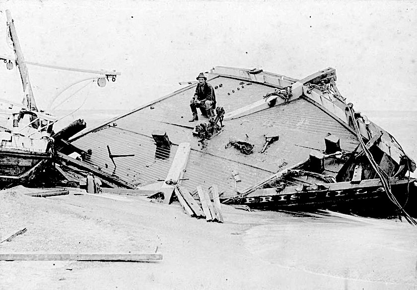 Rasmus Midgett sits on the wrecked remains of the Priscilla. From the H. H. Brimley Collection.