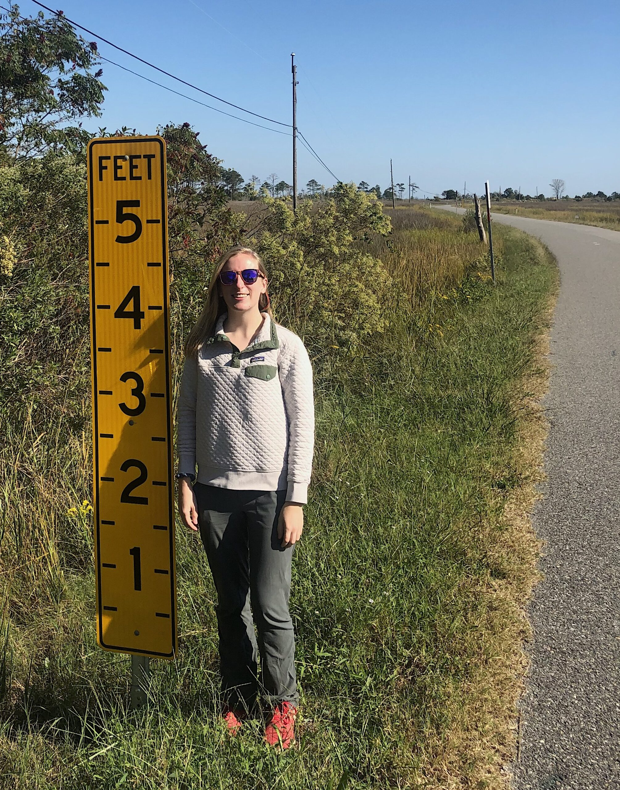 Madison Teeter, next to a sign for measuring flooding in Seaford, Virginia.