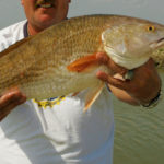 Man holding a red drum
