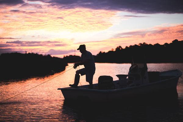 Sillhouette of fisherman on boat pulling a net