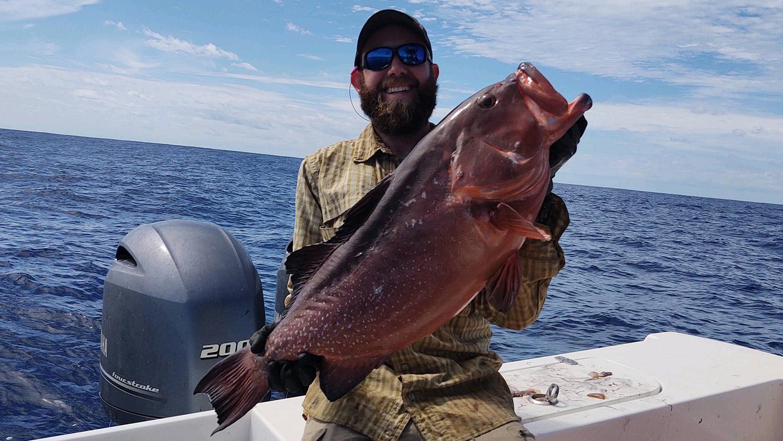 Researcher Brendan Runde holding a red grouper. Photo credit: Owen Mulvey-McFerron.