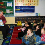 Terri Kirby Hathaway reads to a group of kids.