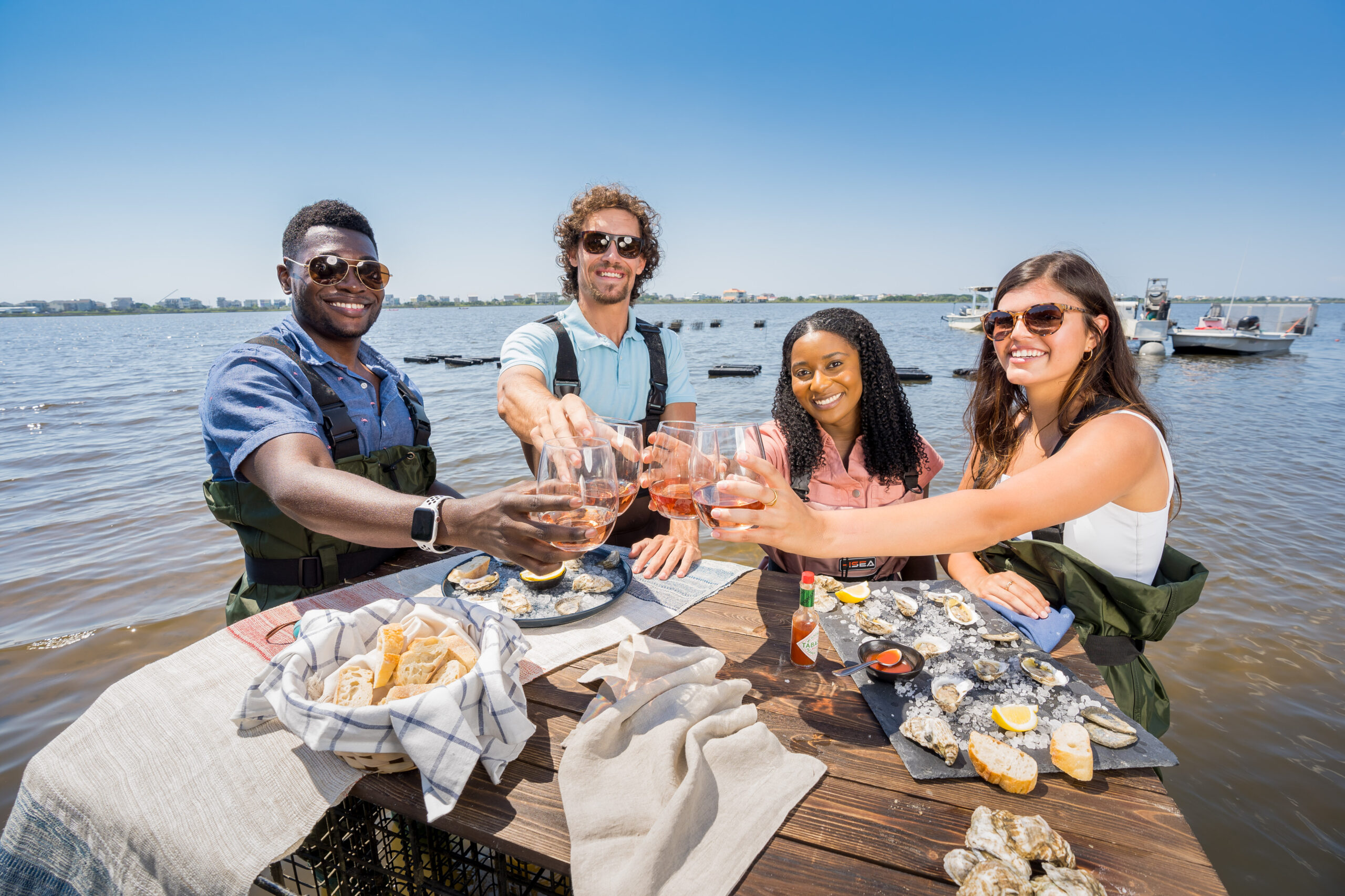 Four people enjoy NC oysters and wine with Stump Sound, N.C., in the background. Photo by Justin Kase Conder