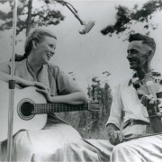 Woman on guitar and man on fiddle, black-and-white photo