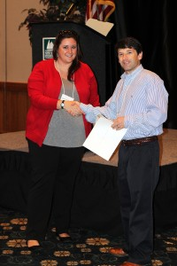 Renee Pellitier accepts the first place poster contest prize from John Fear during the 2016 Graduate Communications Symposium.