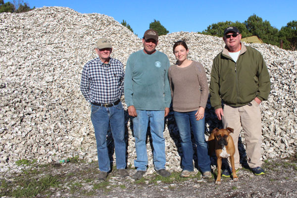 Four people in front of oyster shell piles.