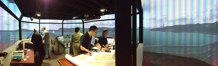 Students working in simulation of ship bridge with Golden Gate Bridge in the background
