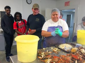 Students watched closely as workers processed crab during a tour of Mattamuskeet Seafood. Cory Carawan, third from left, owns and manages the company with his family.